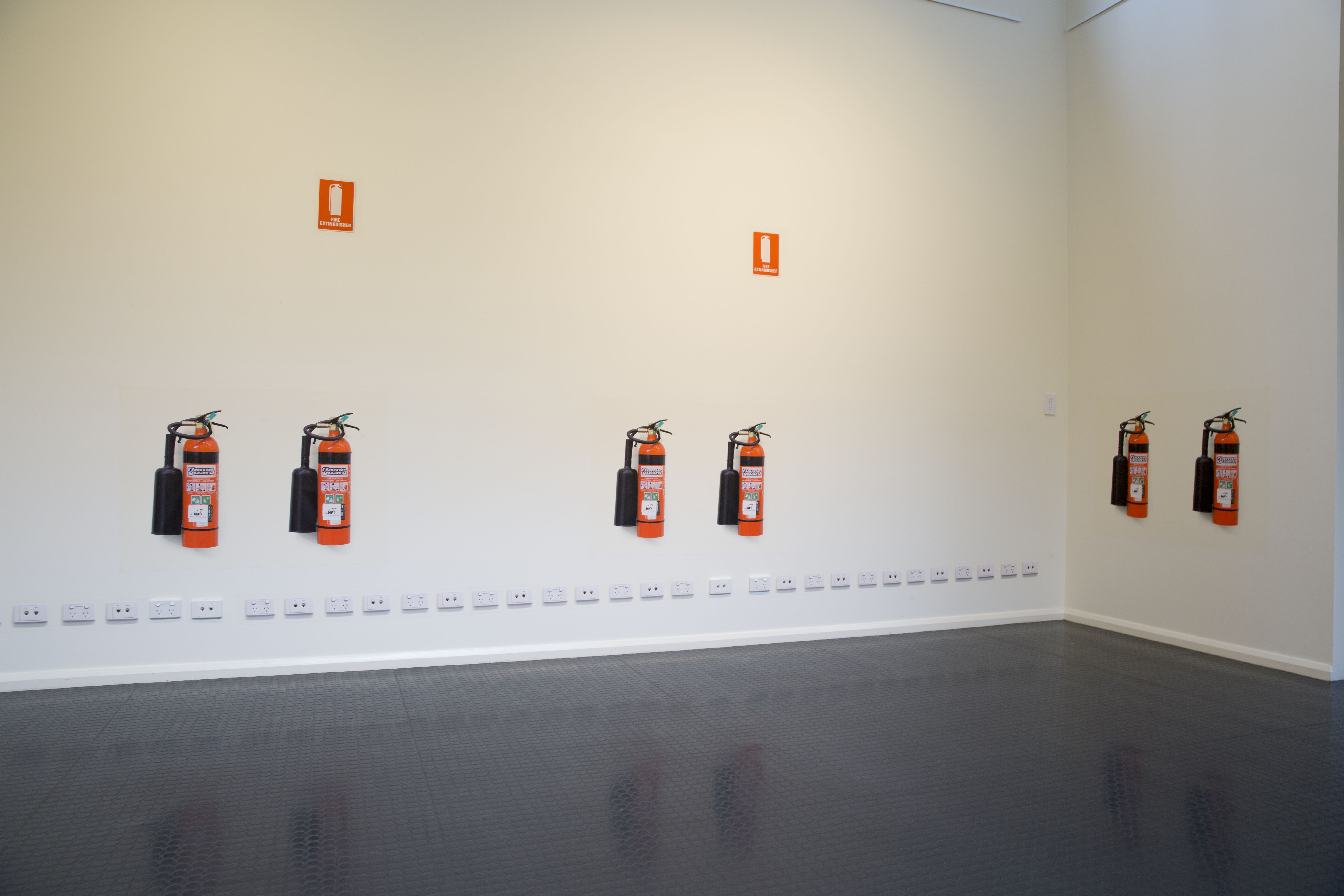 """Figure 13: """"Untitled"""" Digital photographs, hexachrome print on phototex, same-scale as repetitions of fire extinguisher, and fire extinguisher signage. Gallop Gallery, CSU, Wagga Wagga 2013"""