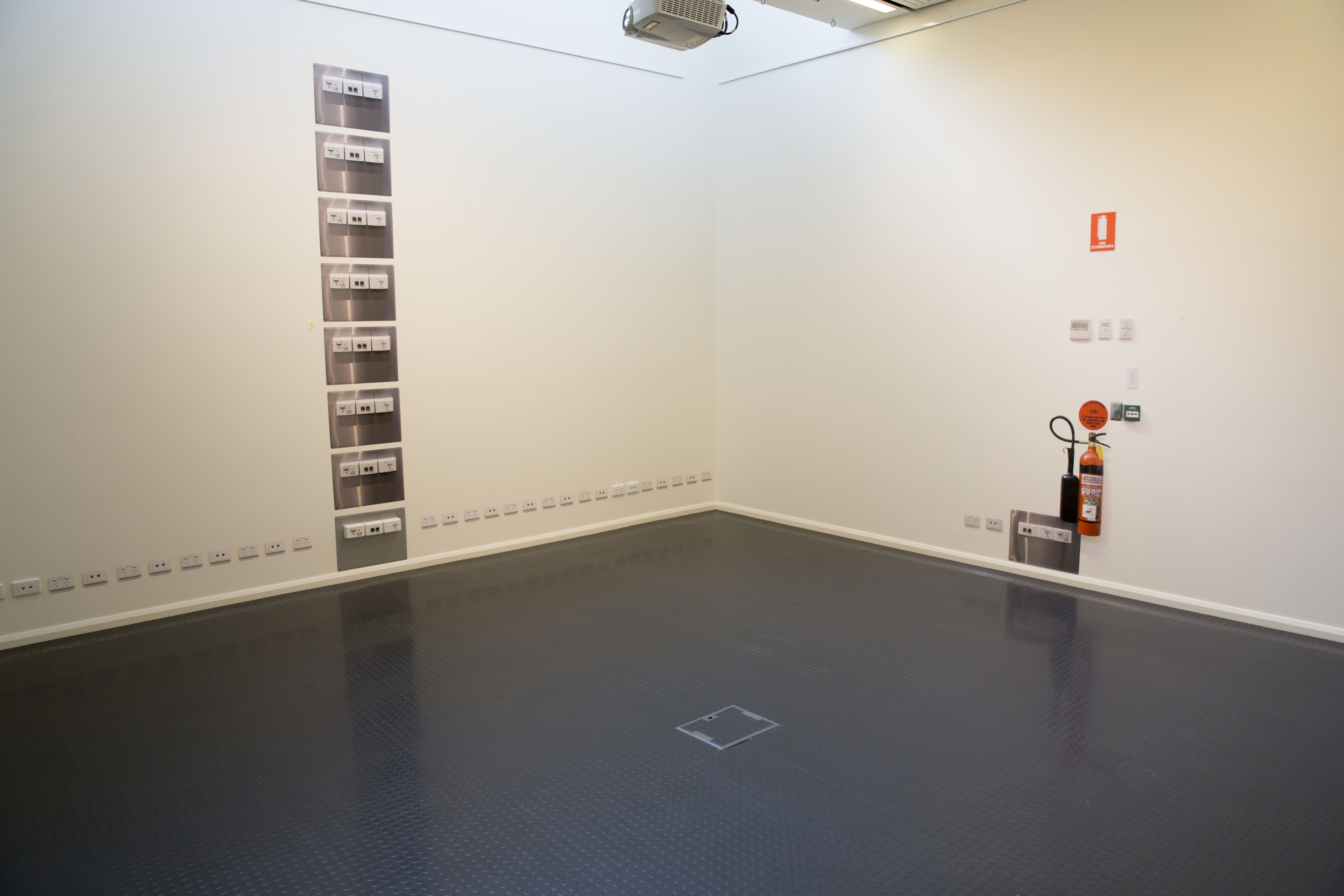 """Figure 4: """"Untitled"""" Digital photographs, hexachrome print on phototex, same scale of power panel fittings (repeated) and fire extinguisher in the Gallop Gallery, CSU, Wagga Wagga, 2013."""