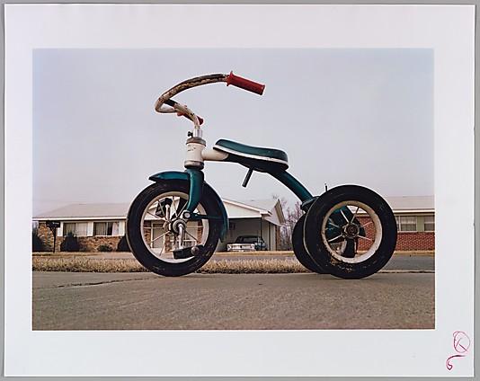 "Figure 3, Willian Eggleston, ""Memphis (Tricycle)"". C. 1969-1970. Dye transfer print. 11.75 x 17.3/8 in. Robert Burge, New York."